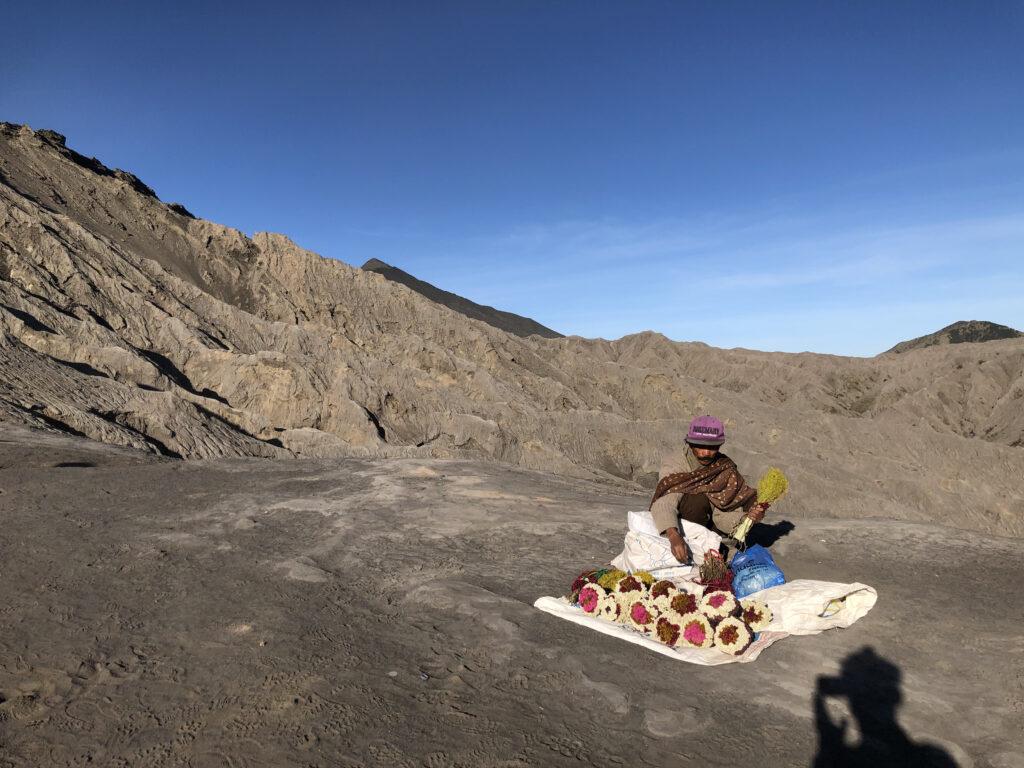 człowiek w górach sprzedaje kwiaty